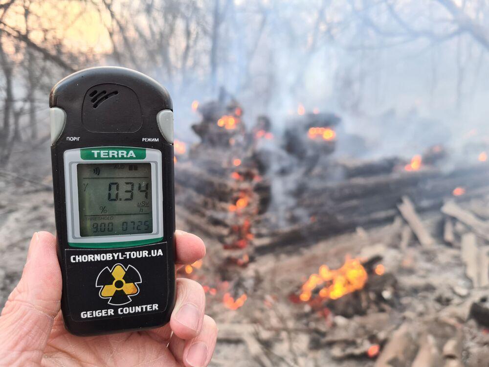 Muž s Geigerovým počítačem během požáru v Černobylské uzavřené zóně