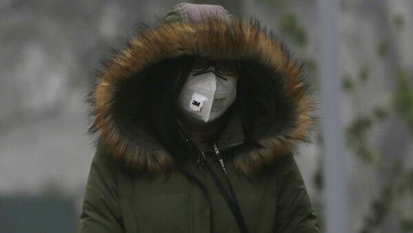 Čínská žena v respirátoru  - Sputnik Česká republika
