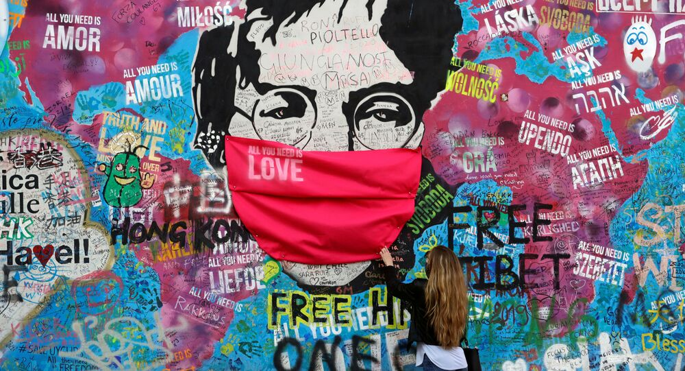 Žena v roušce u Lennonovy zdi v Praze