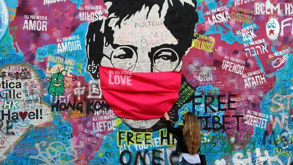 Žena v roušce u legendární zdi Johna Lennona v Praze - Sputnik Česká republika