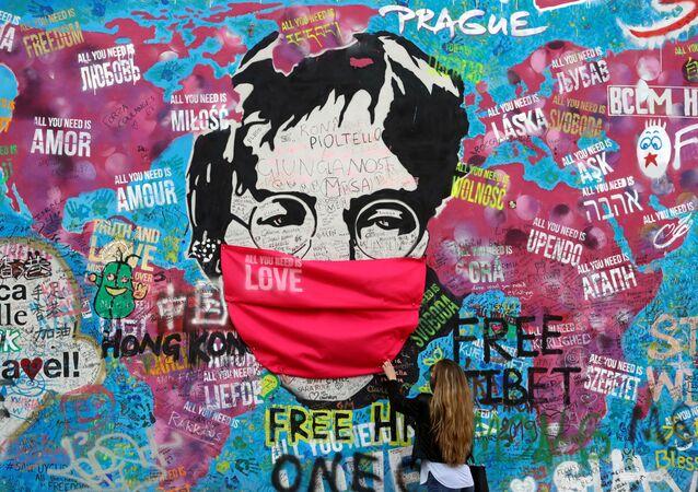 Žena v roušce u legendární zdi Johna Lennona v Praze