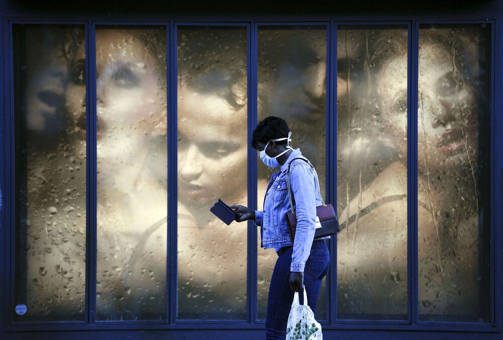 Žena v roušce u výlohy v Paříži, Francie