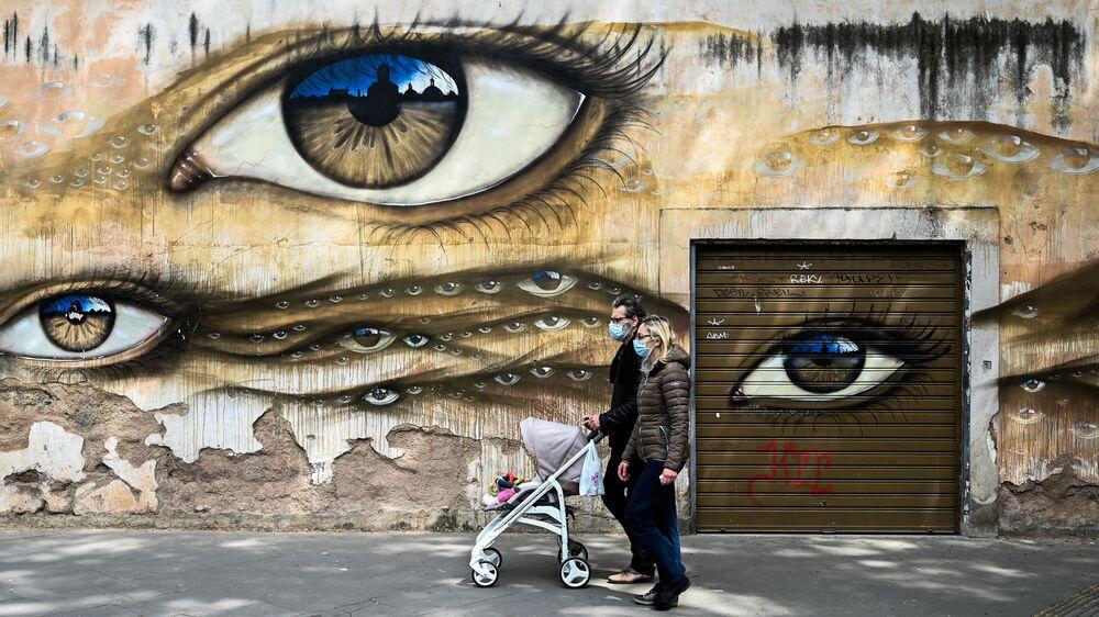 Otec a matka v rouškách s kočárkem na pozadí graffiti v Římě
