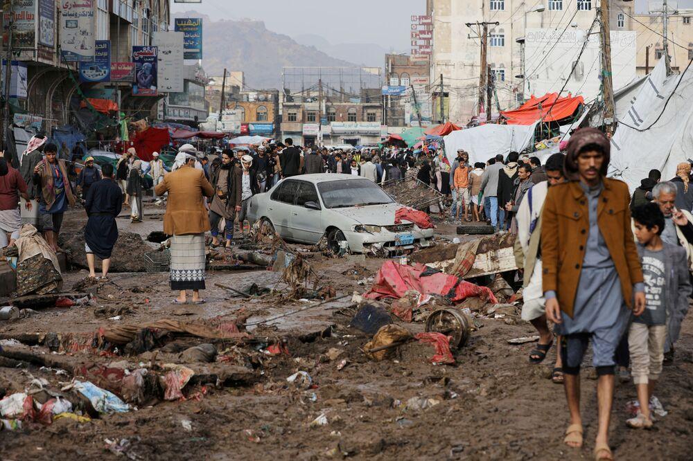 Lidé se procházejí ulicí poškozenou silnými dešti ve městě San'á, Jemen 14. dubna 2020