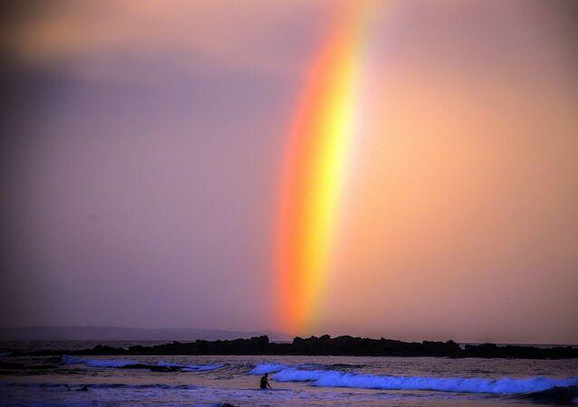 Duha při západu slunce na pláži australského města Mollymook , Austrálie