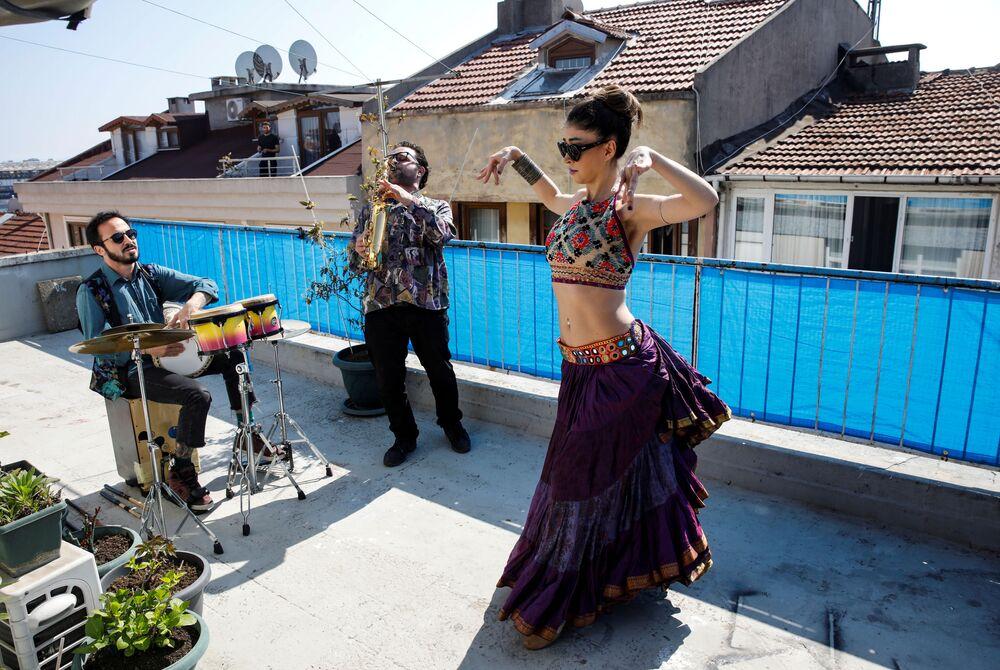 Tanečník vystupuje na terase domu za doprovodu hudebníků v Istanbulu, Turecko