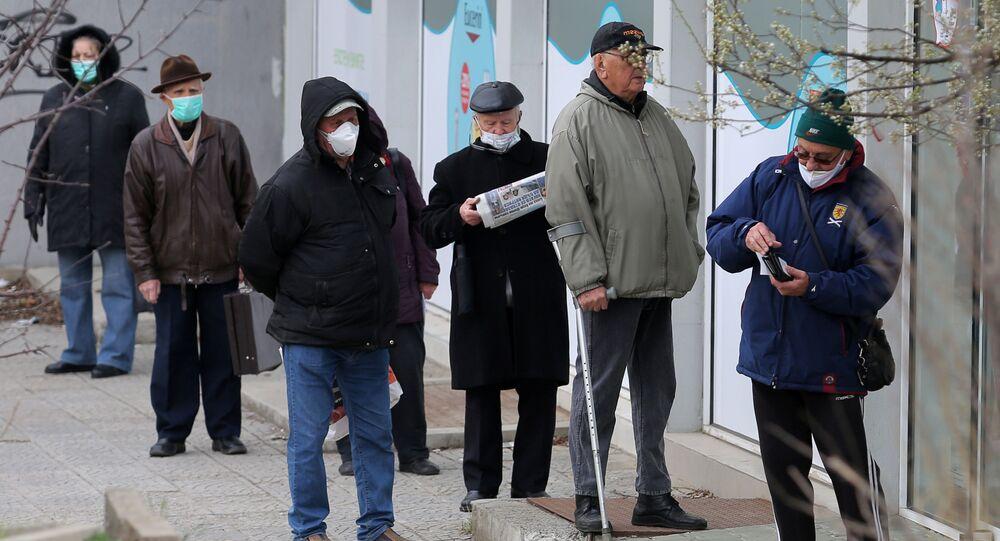 Starší lidé v rouškách poblíž lékárny. Illustrační foto