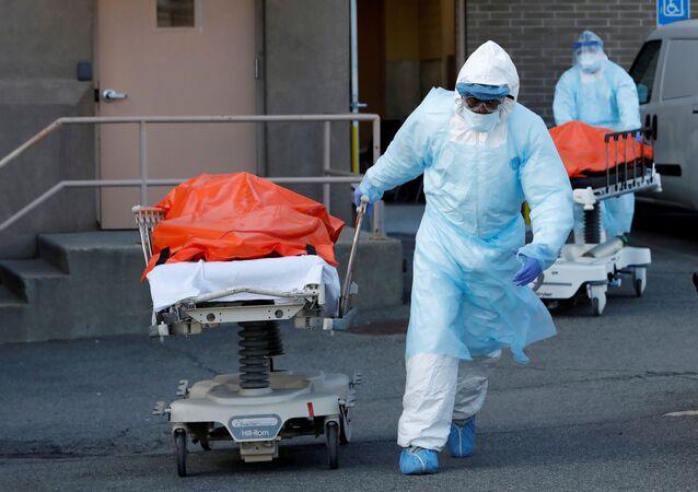 Zdravotníci převážejí mrtvá těla v lékařském centru Wyckoff Heights v New Yorku