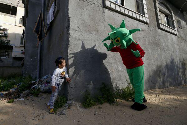 Palestinec v kostýmu koronaviru si hraje s holčičkou v Pásmu Gazy v době pandemie covid-19 - Sputnik Česká republika
