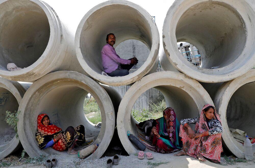 Dělníci-migranti odpočívají v betonových trubkách v Indii