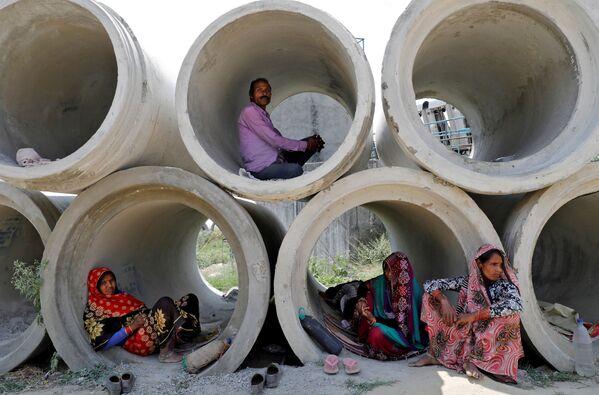 Dělníci-migranti odpočívají v betonových trubkách v Indii - Sputnik Česká republika