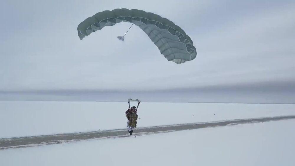 Ruský výsadkář během přistání po hromadnému seskoku z letadla Il-76 v Arktidě