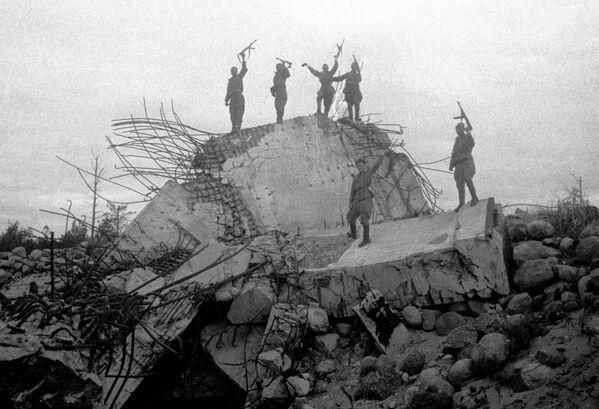 Vojáci Rudé armády stojí na troskách jednoho z německých palebných ohnisek, které bylo zlikvidováno sovětskými jednotkami. Leningradská fronta. - Sputnik Česká republika