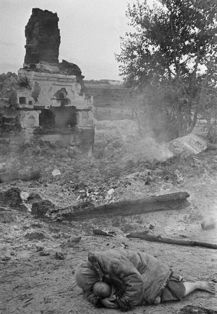 Matka ukrývá své dítě během ostřelování. Vesnice Krasnaja Sloboda, Brjanská fronta, 1941.