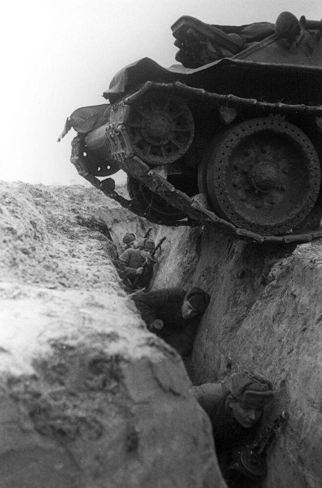 Tank projíždí příkopem s vojáky během cvičení.