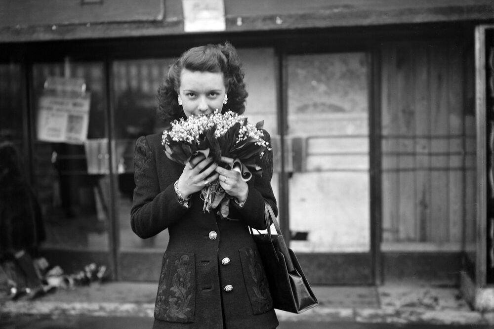 Dívka drží v ruce konvalinky, Paříž, 1. května 1945