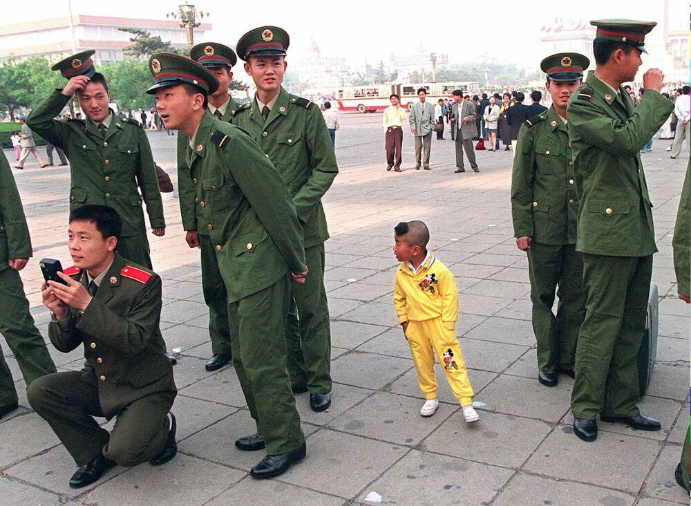 Chlapec ve skupině čínských vojáků 1. května 1997 v Pekingu