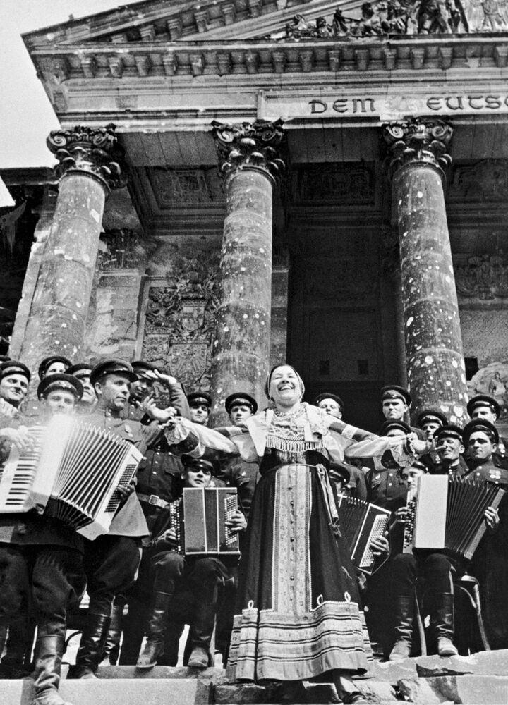 Sovětská zpěváčka Lidia Ruslanova zpívá před sovětskými vojáky na schodech Říšského sněmu.