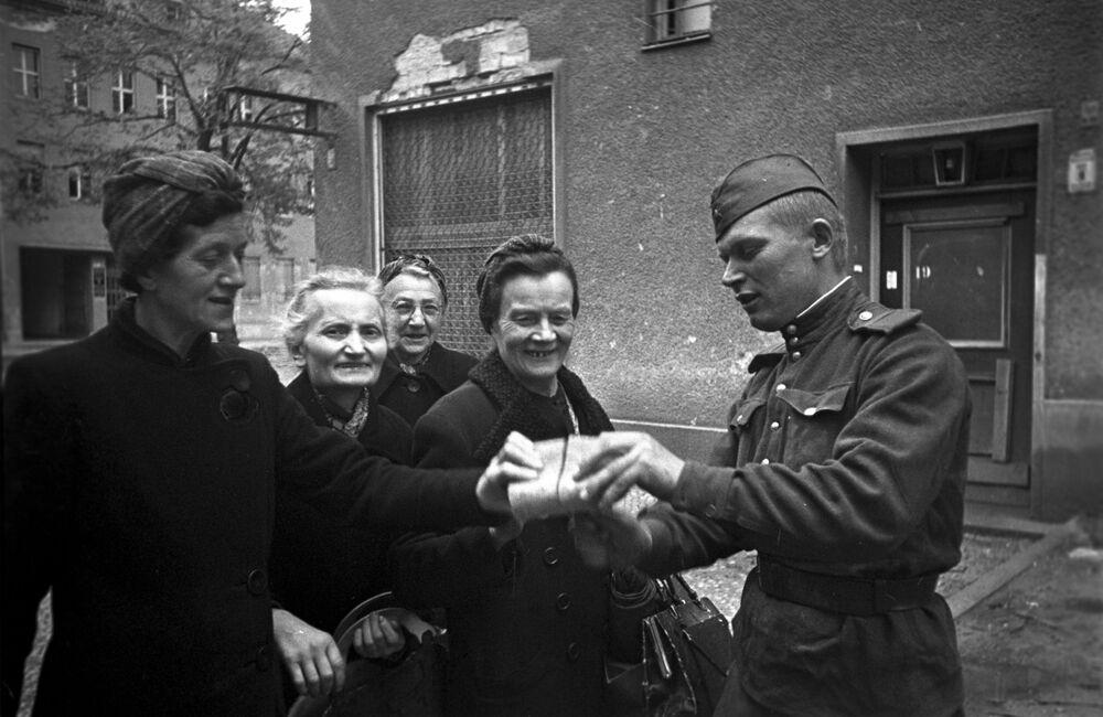 Sovětský voják rozdává chléb ženám v Berlíně.