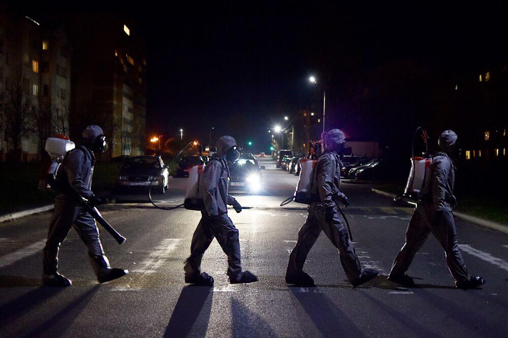 Beatles to není: Běloruští vojáci přecházejí po přechodu poté, co provedli dezinfekci v nemocnici poblíž Minsku.