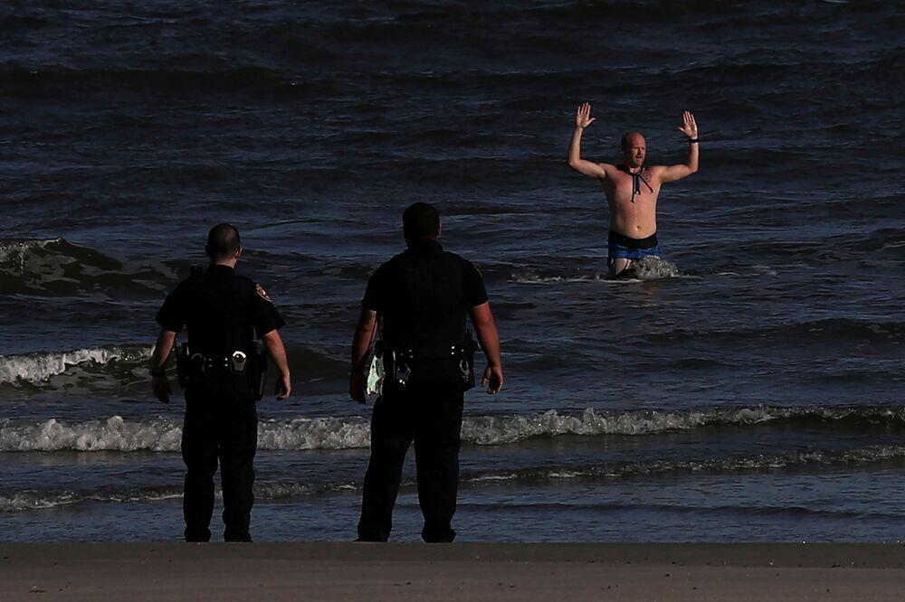 Muž obklíčený policií s rukama nad hlavou vystupuje z moře na pláži v texaském městě Galveston.