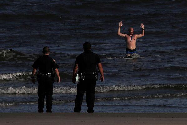 Muž obklíčený policií s rukama nad hlavou vystupuje z moře na pláži v texaském městě Galveston. - Sputnik Česká republika