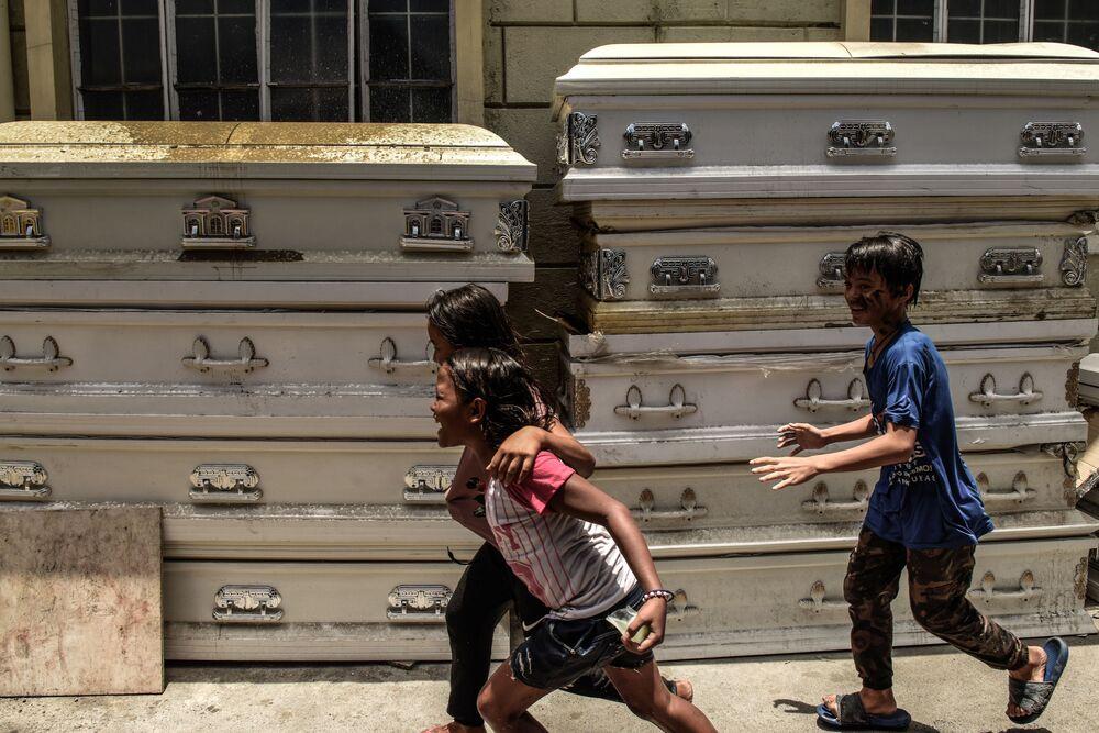 Děti si hrají vedle rakví v Manile. Na většině území Filipín byla vyhlášena karanténa. Nemoc byla zaznamenána u více než devíti tisíc lidí. Přinejmenším 600 z nich zahynulo.