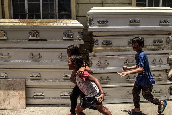 Děti si hrají vedle rakví v Manile. Na většině území Filipín byla vyhlášena karanténa. Nemoc byla zaznamenána u více než devíti tisíc lidí. Přinejmenším 600 z nich zahynulo. - Sputnik Česká republika