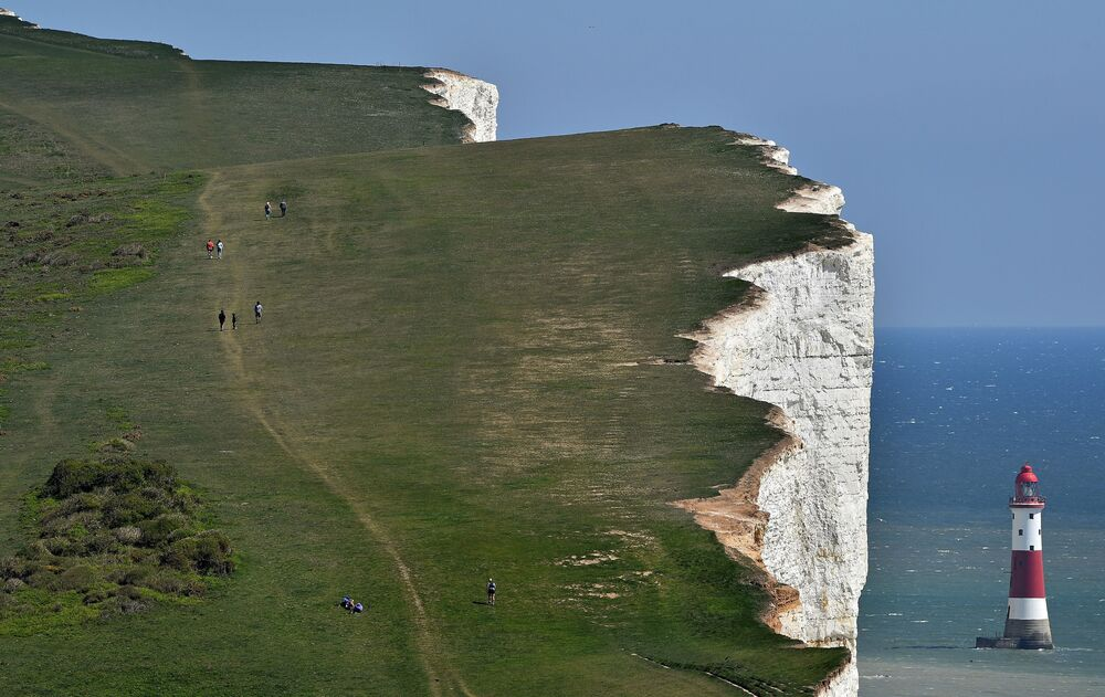 Lidé se procházejí po křídovém mysu Beachy Head na jižním pobřeží Anglie.