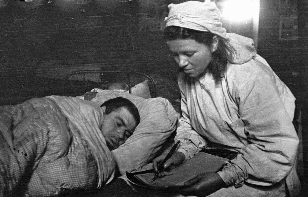 Zdravotní sestra píše dopis, který jí diktuje zraněný voják