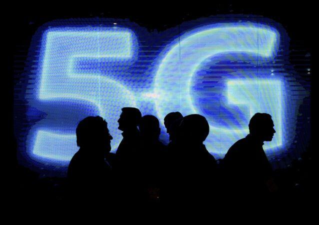 Návštěvníci naproti logu 5G na výstavě mobilního průmyslu Mobile World Congress