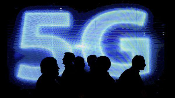 Návštěvníci naproti logu 5G na výstavě mobilního průmyslu Mobile World Congress - Sputnik Česká republika