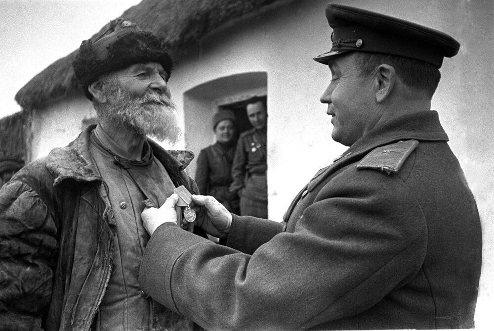 Velitel divize uděluje kolchozníkovi Pomkinovi odměnu za hrdinství, 3. ukrajinský front. 1945