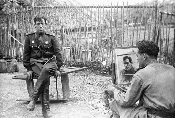 Umělec Nikolaj Sokolov maluje portrét poručíka N. Bryskina, 1944 - Sputnik Česká republika