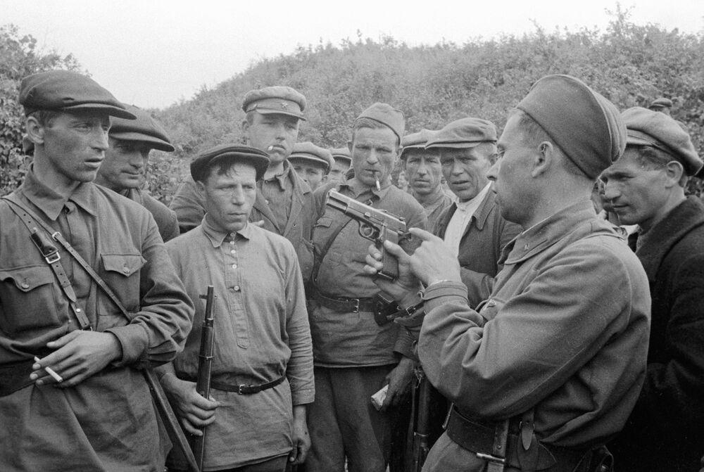 Velitel partyzánské jednotky ukazuje bojovníkům zbraně. Smolenská oblast, Rusko, 1941