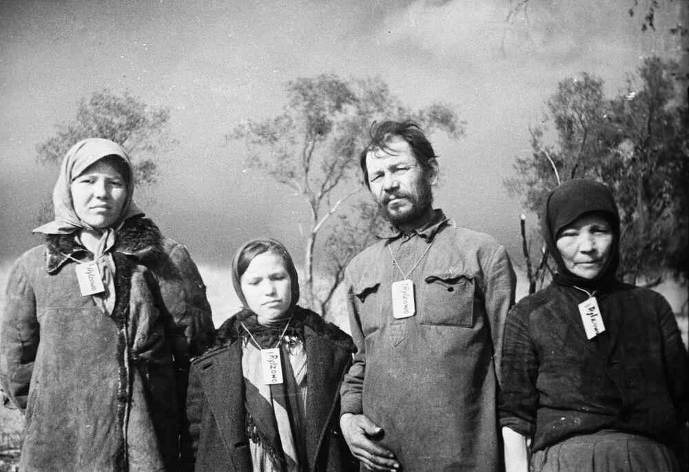 Obyvatelé obce Zubcovo. V okupovaných vesnicích nacisté nutili obyvatelstvo nosit štítky kolem krku se jménem vesnice, kde žijí, 1941