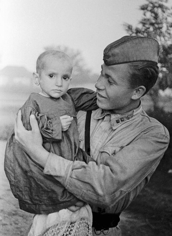 Sovětský voják drží v náručí dívku, kterou zachránil, 1942
