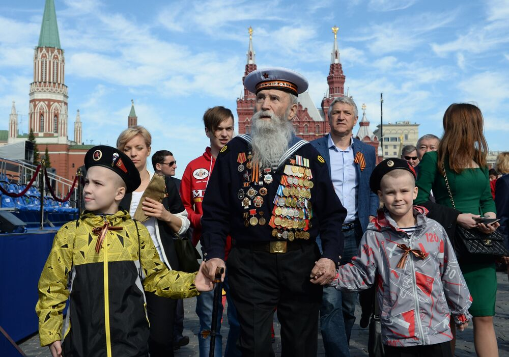Veterán s dětmi před zahájením vojenského průvodu u příležitosti 70. výročí vítězství ve Velké vlastenecké válce.