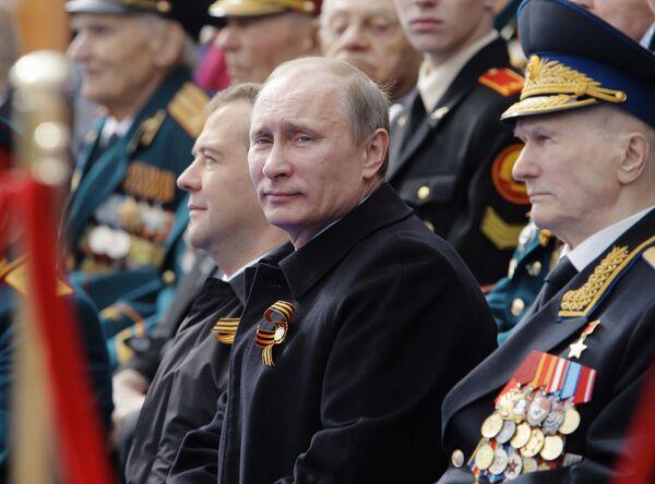 Tehdejší prezident Dmitrij Medveděv a ruský premiér Vladimir Putin na Rudém náměstí na vojenské přehlídce v roce 2011. - Sputnik Česká republika