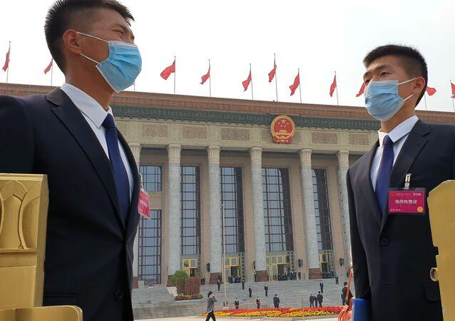 Příslušníci bezpečnostních složek před zasedáním Národního výboru Čínského lidového politického poradního shromáždění Číny v Pekingu