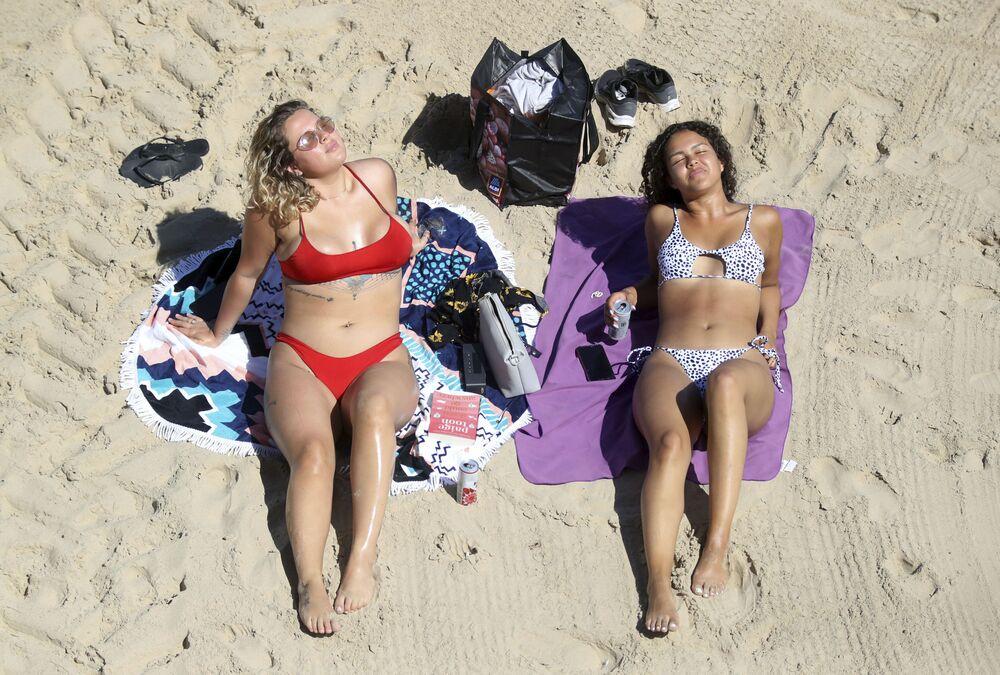 Dvě dívky se opalují na pláži Cullercoats, Anglie