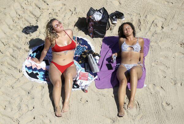 Dvě dívky se opalují na pláži Cullercoats, Anglie - Sputnik Česká republika