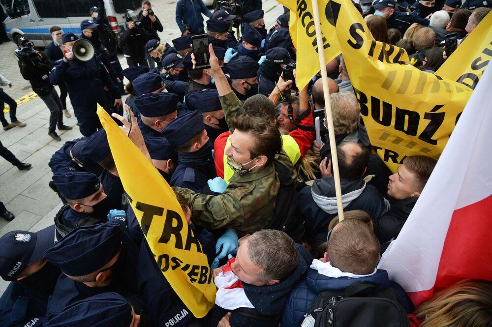 Demonstranti protestují proti karanténním opatřením uloženým v souvislosti s pandemií koronaviru COVID-19 s policisty ve Varšavě