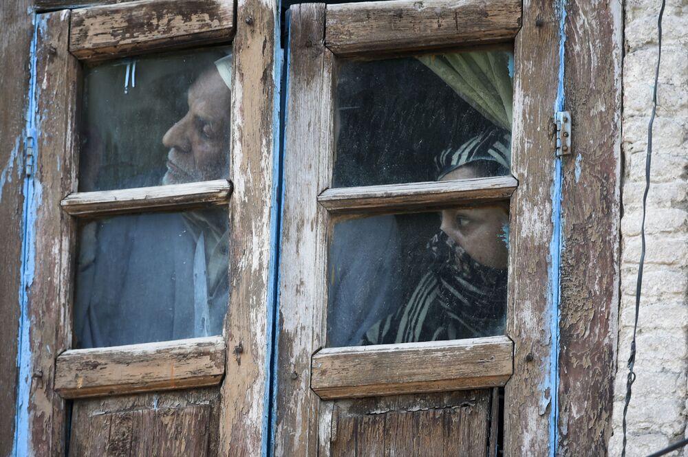 Lidé se dívají z okna svého domova v Srinagaru, Indie