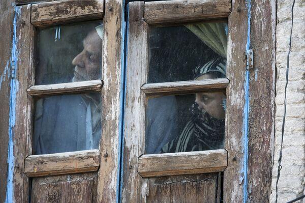 Lidé se dívají z okna svého domova v Srinagaru, Indie - Sputnik Česká republika