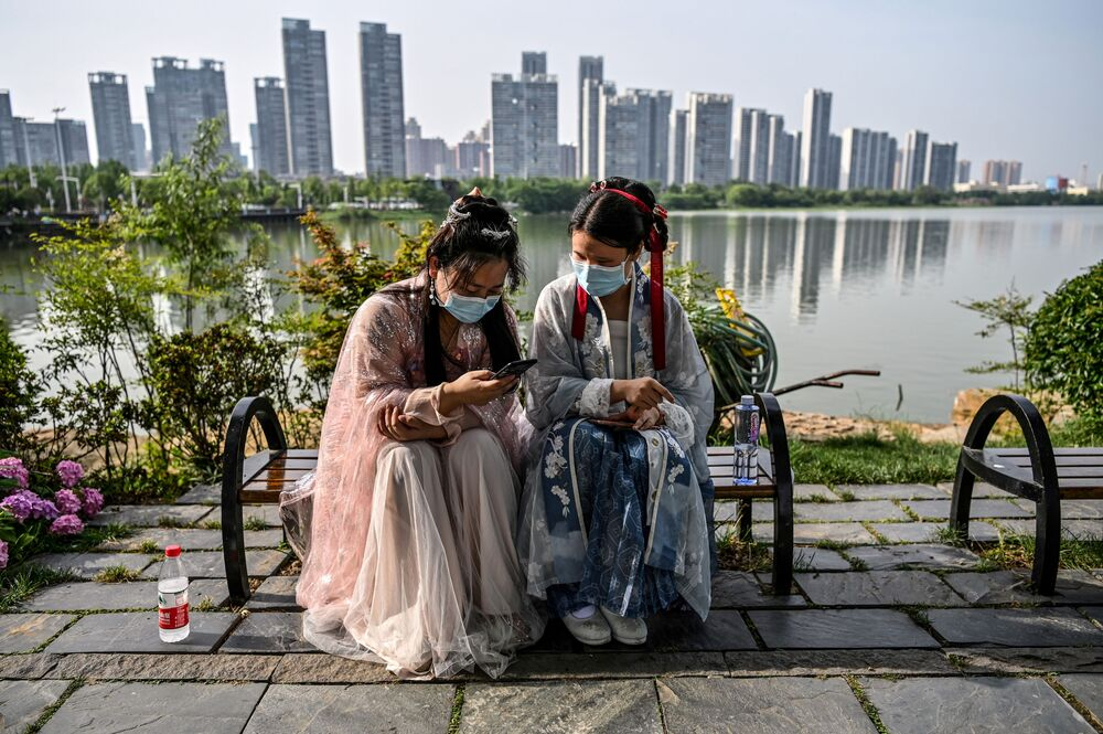 Mladé ženy v maskách a tradičních kostýmech na lavičce ve Wuhanském Parku, Čína