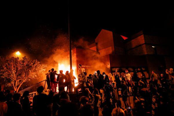 Protestující lidé poblíž hořící stanice v Minneapolisu, stát Minnesota, USA - Sputnik Česká republika