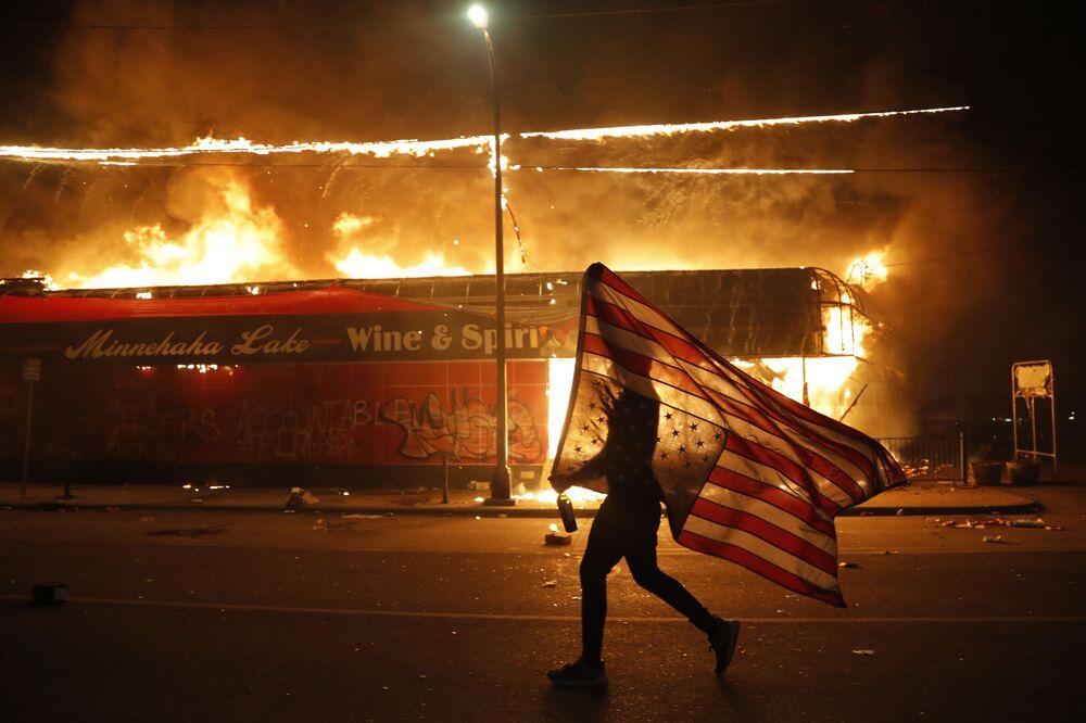 Demonstrant s vlajkou poblíž hořící stanice v Minneapolisu, stát Minnesota, USA