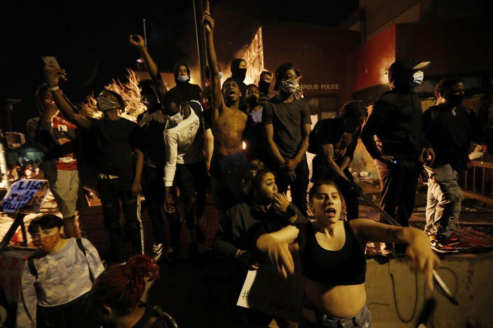 Protestující lidé poblíž hořící stanice v Minneapolisu, stát Minnesota, USA