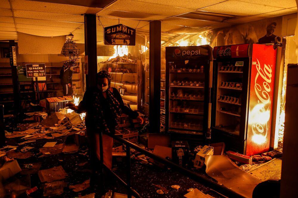 Žena ve vypáleném obchodě v Minneapolisu, stát Minnesota, USA